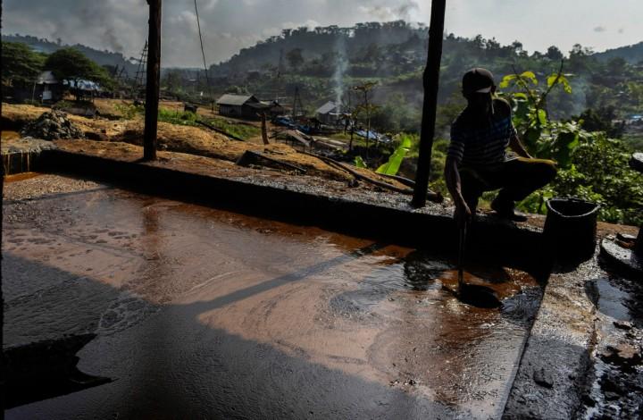 Penambang mengambil minyak mentah untuk dipindahkan ke wadah penyimpanan di penambangan minyak rakyat, Wonocolo, Bojonegoro, Jawa Timur.