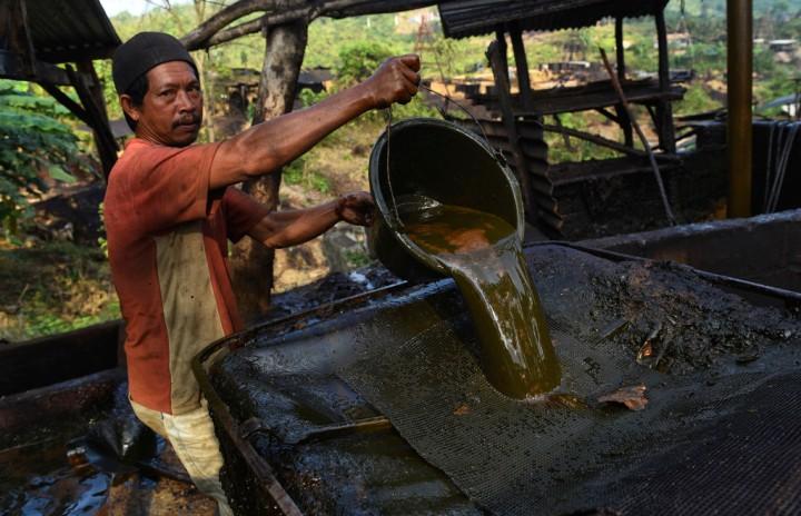 Penambang menunjukkan minyak mentah hasil tambangnya di penambangan minyak rakyat, Wonocolo, Bojonegoro, Jawa Timur.